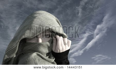 Asian woman in yashmak over the sky background