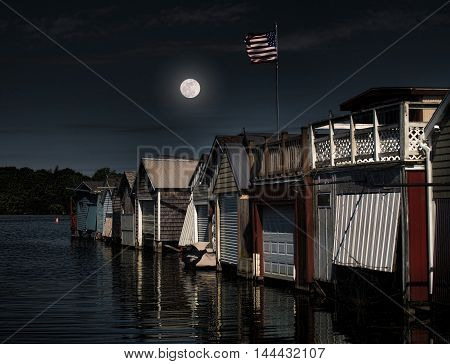 moon over old boathouses with American flag