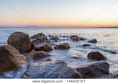 Landscape With Rocks And Waves At Sunset
