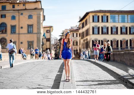 Beautiful female traveler in blue dress, hat and backpack walking on crowded Holy Trinity bridge in Florence city. Vacation in Italy
