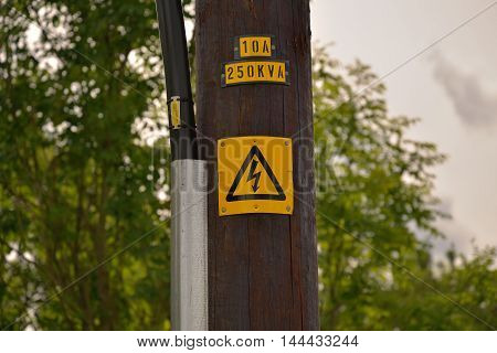 The warning signage on the wooden electric pole represent the sign and symbol concept related idea.