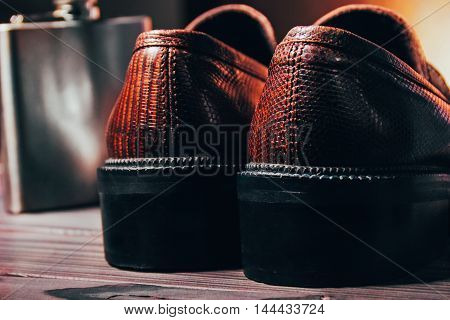 Behind Mocasine Shoes Of Snake Skin And Stainless Flask On Fir