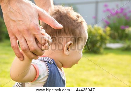father and young son. Closeup of how the supports the baby when he makes first steps. male hands holding small 's . concept family