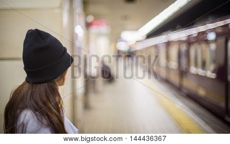 A girl is waiting for Subway train in Japan