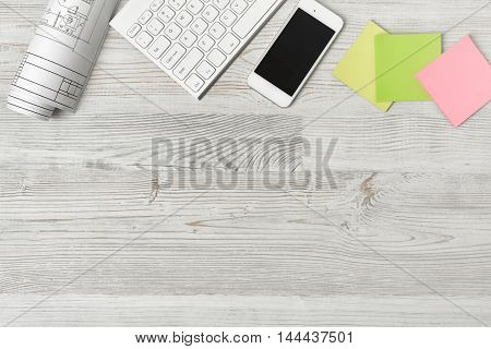 Top view of a workplace with a paper roll, a keyboard, a smartphone and stickers on a wooden table. Office workplace. Creative minimalism. Design and creativity. Workspace. View with copyspace.