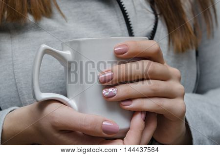 Beautiful female hand with warm pink nail design holdinbg a white cup.