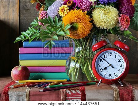 Bouquet and book. Back to school. Still life with a stack of books alarm clock and colored pencils.