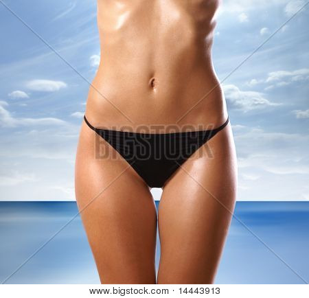 Belly of beautiful woman over abstract resort background