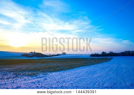 View of a sunset over a winterly landscape in a rural environment in Germany, Europe.