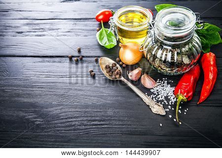 And spice still life of seasoning pepper salt on old black wooden board in rustic style