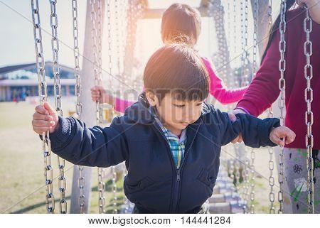 Asian Kids walking across Obstacle Bridge playground