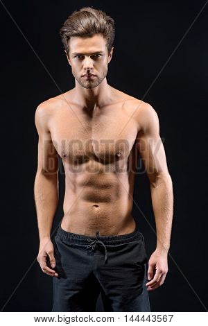 Handsome young man with naked torso standing and posing. He is looking at camera with confidence. Isolated on black background