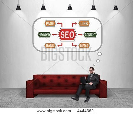 businessman working sitting on red sofa and thinking about seo concept
