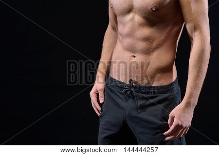 Close up of bare male muscular torso. Strong man is standing and posing. Isolated and copy space in left side