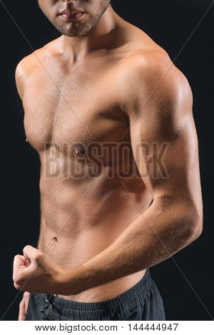 I am very strong. Young bodybuilder is showing raising hand and showing his muscles. Isolated on black background