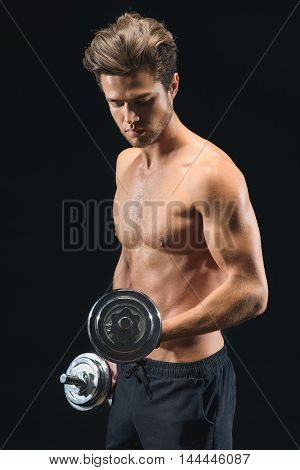 Confident young sportsman is training his body with dumbbells. He is standing and looking at his bicep with satisfaction. Isolated on black background