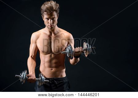 Strong young man is lifting heavy dumbbells with confidence. Isolated and copy space in right side