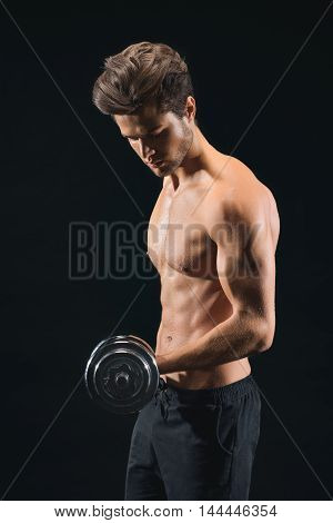 Cheerful young man is training bicep with dumbbell. He is standing and looking at weight with concentration. Isolated on black background