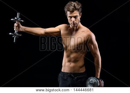 Strong young man is standing and holding dumbbells. He is stretching arm sideways and looking at camera with confidence. Isolated on black background