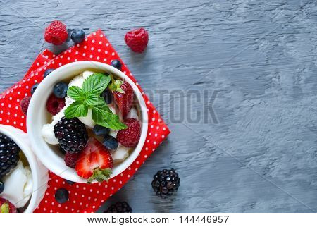 Vanilla ice cream with blueberries raspberries and strawberries with mint on a concrete background