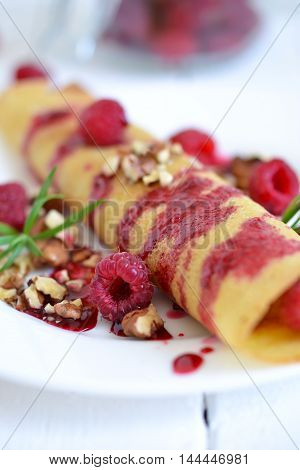 Pancakes with fresh raspberries nuts and raspberry sauce