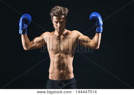 Fit confident young man is raising arms and flexing muscles. He is standing and wearing boxing gloves. Isolated