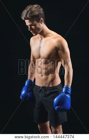 Young boxer is preparing for fight. Man is standing and looking down with concentration. Isolated on black background
