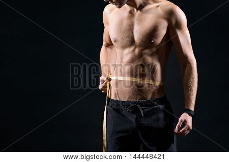 Strong male athlete is measuring his waist with tape. He is standing with naked torso. Isolated and copy space in left side