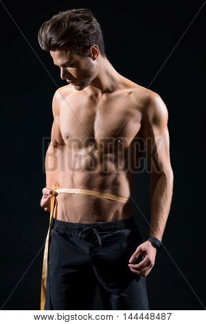 Attractive young man is taking measurements of his trained abdomen. He is standing and looking at tape with concentration. Isolated on black background