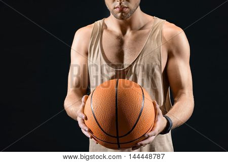 Confident young man is playing basketball. Isolated on black background