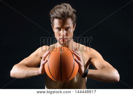 Professional sportsman is ready to throw ball in basket. He is standing and looking forward with desire. Isolated