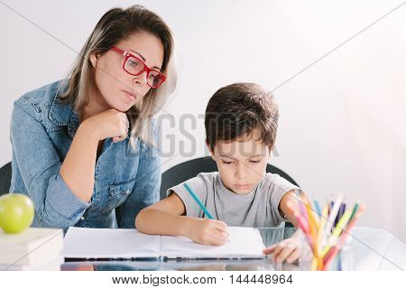 Young Mother Sitting At A Table At Home Helping Her Small Son With His Homework From School As He Wr