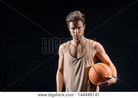 Passionate young basketball player is standing and holding ball. He is looking at camera with aspiration. Isolated and copy space in left side