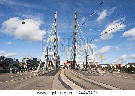 Tall white suspension bridge with tram rails
