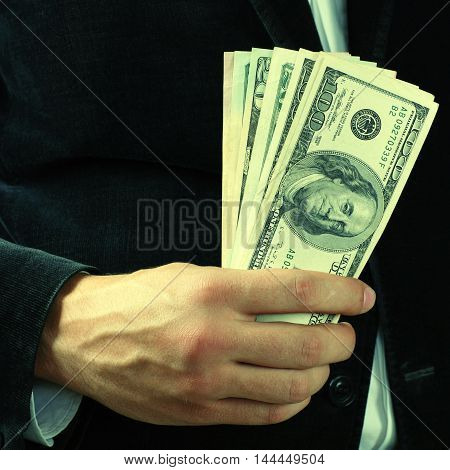 man holding a stack of dollar banknotes, square toned image