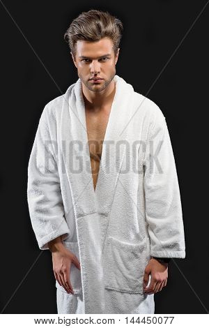 Attractive young man is standing and relaxing. He is wearing white bathrobe. Man is looking at camera with seriousness. Isolated