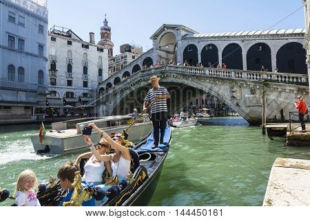 VENICE,ITALY-AUGUST 17,2014:Two girls take a salfie on the venetian gondola with Rialto bridge on background during a sunny day.