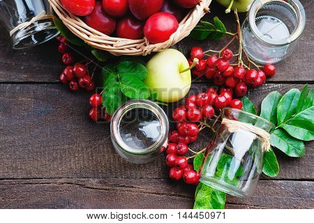Plums in a basket, apples, rowanberry and glass jars