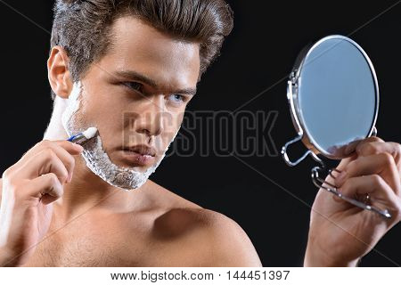 Confident young man is shaving his stubble in front of mirror. He is gliding razor on foam. Isolated
