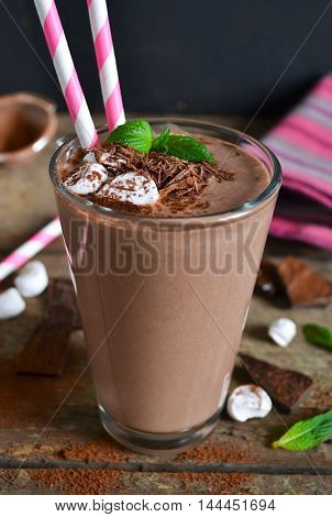 Chocolate smoothie with banana oatmeal almonds and marshmallow wooden background