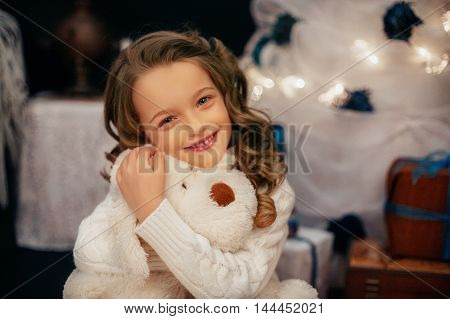 sweet little girl embraces emotionally bag. The concept of the New Year and Merry Christmas
