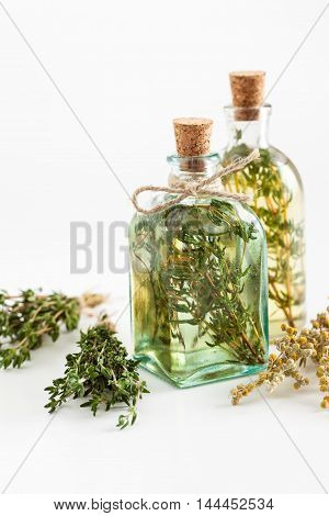 Bottles of thyme and rosemary essential oil or infusion and bunches of healthy herbs on white herbal medicine.