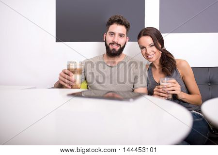 A nice young couple sitting at the table in a coffee shop and enjoying coffee.