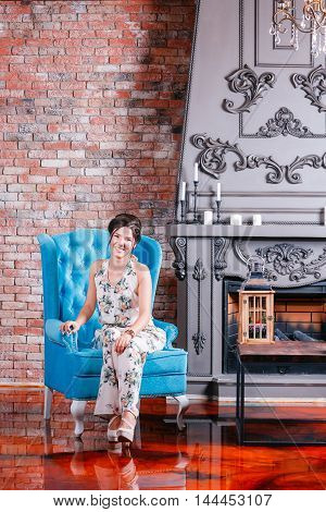 Beautiful woman with blue eyes and curly hair in dress on luxory interer background the fireplace chandelier. blue sofa.