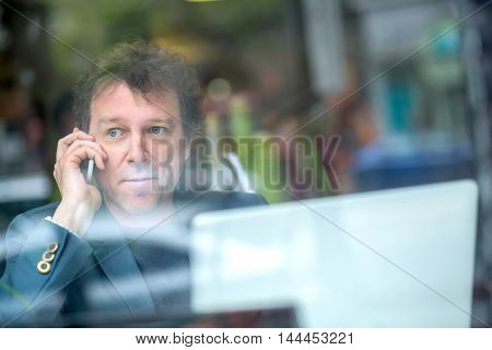 Portrait of a middle age businessman siting in the window of a coffee shop and speaking on the phone.