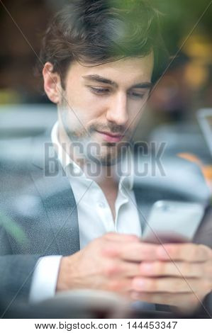 A handsome young businessman siting in the window of a coffee shop and using his phone.