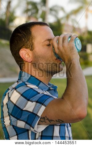 Young man drinking from a cup outside at a park wearing a plaid shirt.
