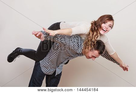 Smiling woman riding piggyback on man shoulders. Happy young couple having fun together in studio on gray.
