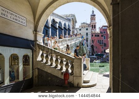 VENICE,ITALY-AUGUST 17,2014:people and tourist stroll and take photo on the Rialto bridge in Venice during a sunny day.
