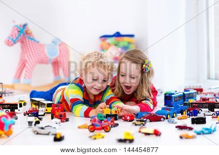 Little toddler boy and girl playing with model car collection on the floor. Transportation and rescue toys for children. Toy mess in child room. Many cars for little boys. Educational games for kids.